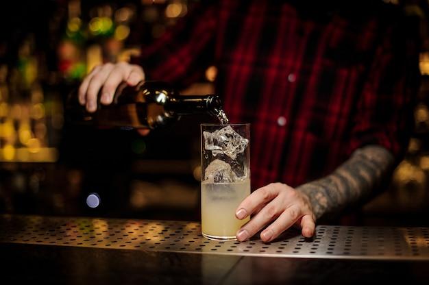 Mixólogo vertiendo bebida alcohólica de botella en una copa de cóctel con jugo y cubitos de hielo