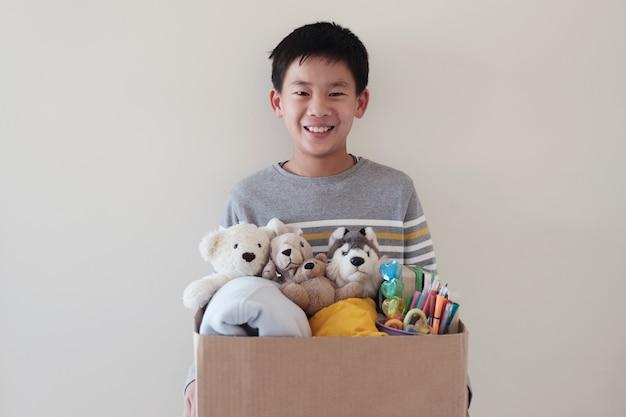 Mixto asiático joven voluntario preadolescente adolescente sosteniendo una caja llena de juguetes usados