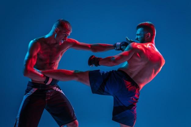 Mma. dos luchadores profesionales de perforación o boxeo aislado en la pared azul en neón