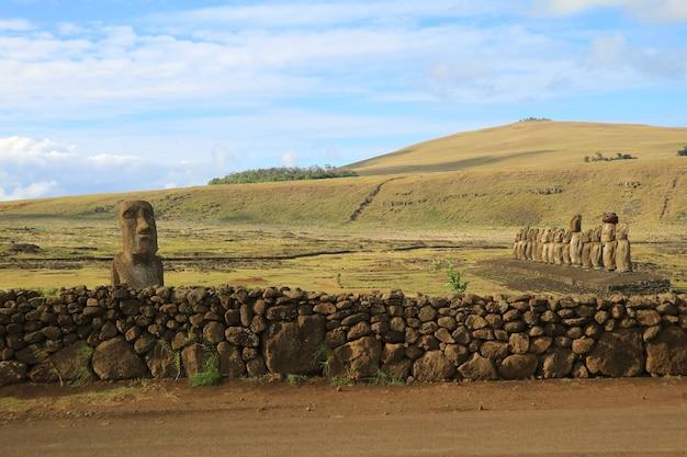 Moai solitario cerca de valla de piedra y 15 moai en la plataforma en ahu tongariki, isla de pascua, chile