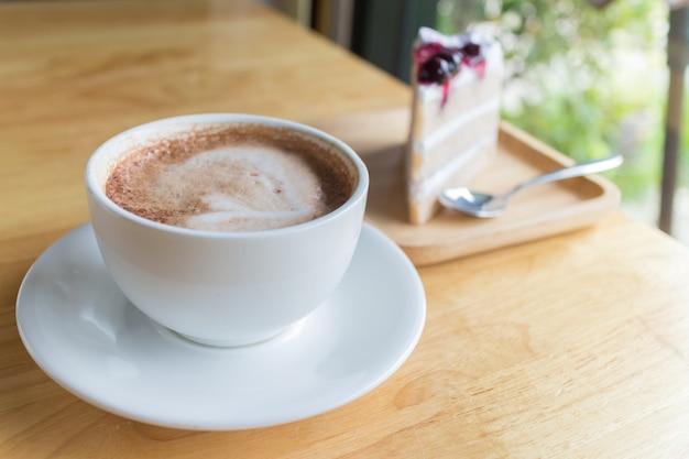Moca de café caliente con leche de espuma y pastel de arándanos en café de campo