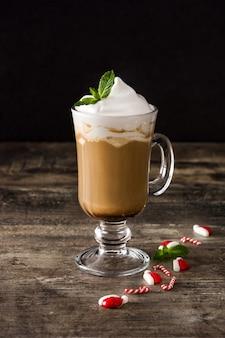 Moca de café de menta para navidad en mesa de madera y negro