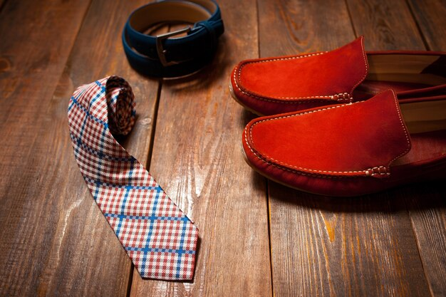 Mocasines terracota cinturón azul lazo cuadros. mirada masculina casual.