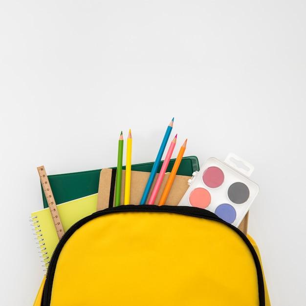 Mochila abierta con accesorios escolares.