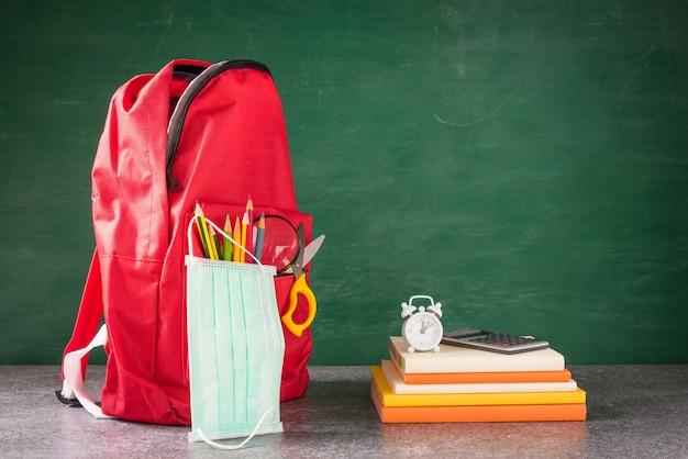La mochila y los accesorios de la escuela delantera con mascarilla protegen en la mesa en la pizarra