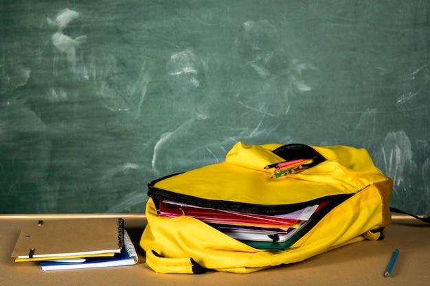 Mochila amarilla abierta con cuadernos.