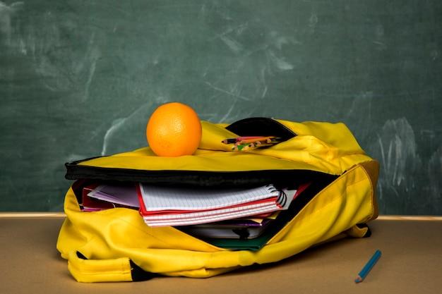 Mochila amarilla con cuadernos y naranja.