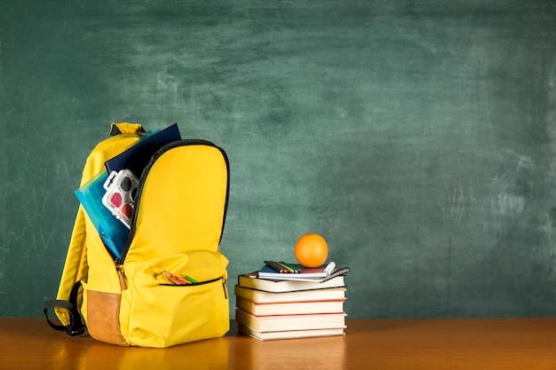 Mochila amarilla con papelería y libros apilados.