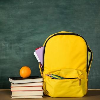 Mochila amarilla, pila de libros y naranja.