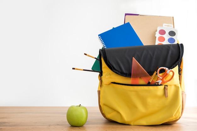 Mochila amarilla con útiles escolares y manzana.
