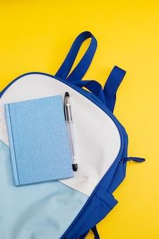 Mochila azul y blanca sobre fondo amarillo