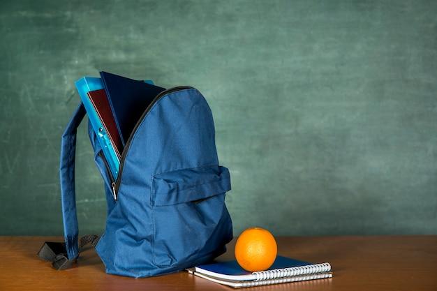 Mochila azul con cuaderno y naranja