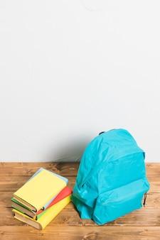 Mochila azul con libros con tapa en blanco sobre mesa de madera