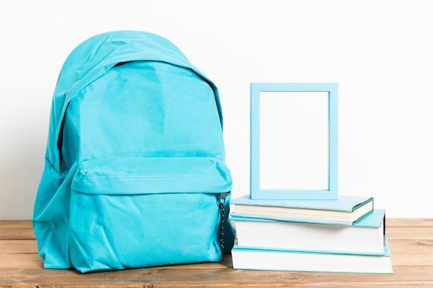 Mochila azul con marco vacío en libros sobre mesa de madera
