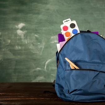 Mochila azul con papelería y acuarelas.