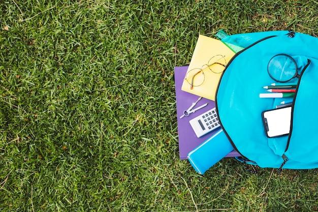 Mochila azul con papelería y teléfono inteligente.
