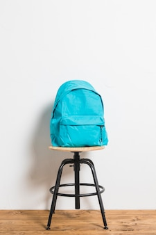Mochila azul en silla taburete sobre superficie de madera