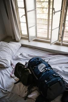 Mochila en una cama en una habitación de hotel por la mañana.