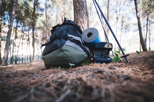 Mochila y cámara cerca de un árbol