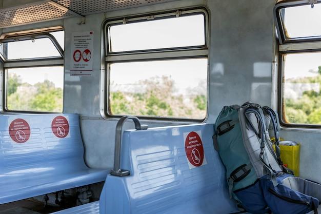 Mochila con cosas en el asiento de un tren con marcas para la distancia de los pasajeros. turismo y viajes.