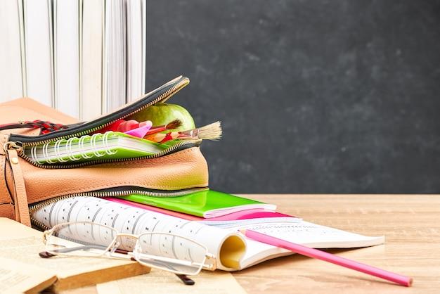 Mochila con cuadernos y bolígrafos en el fondo de la pizarra