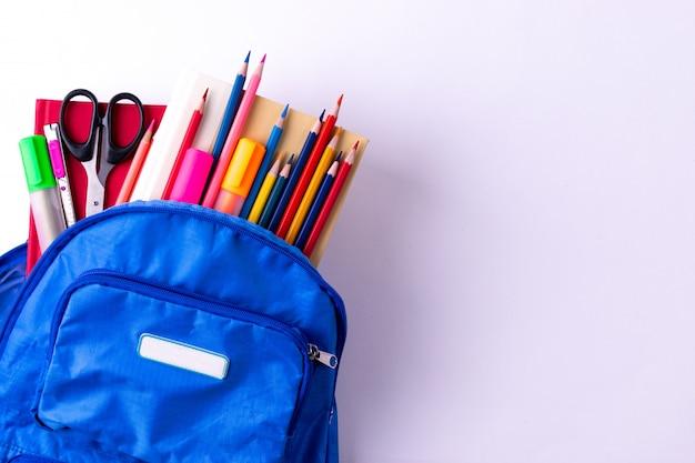 Mochila con diversos efectos de escritorio coloridos en la tabla blanca. volver al concepto de escuela.