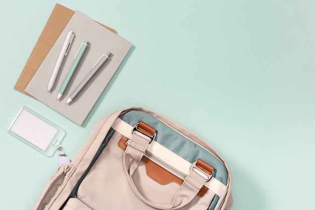 Mochila escolar y accesorios escolares, cuadernos, bolígrafos, insignia de colegial sobre fondo neo menta.