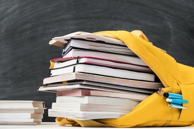 Mochila escolar amarilla brillante llena de libros