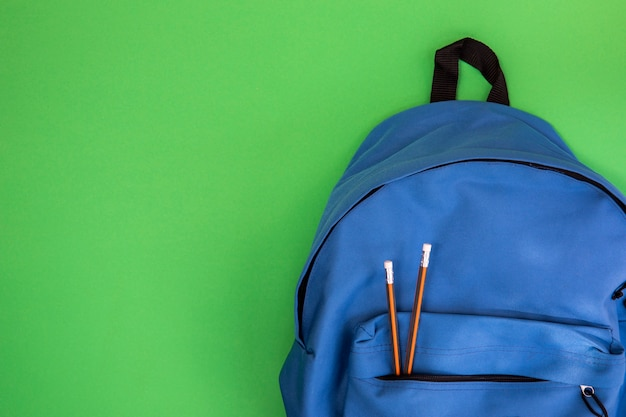 Mochila escolar azul con lápices.