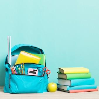 Mochila escolar azul con útiles y libros de texto.