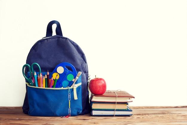 Mochila escolar completa con libros y manzana en blanco.
