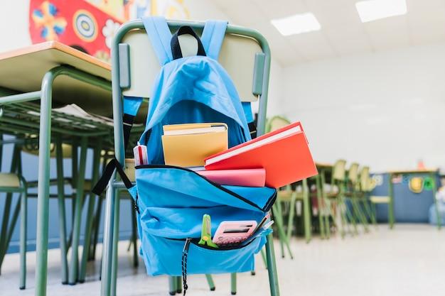 Mochila escolar con libros de texto en silla.
