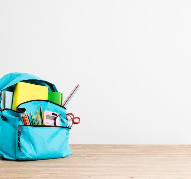 Mochila escolar llena de papelería y libros azul.