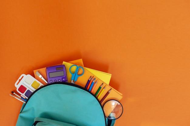 Mochila escolar turquesa completa con diferentes suministros sobre fondo naranja.