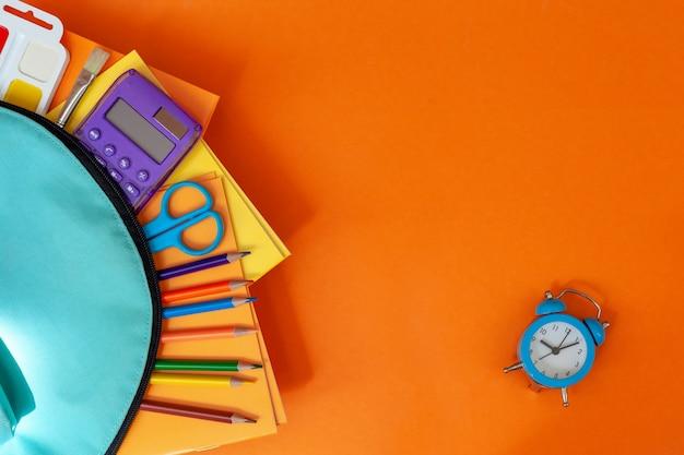 Mochila escolar turquesa completa con suministros sobre fondo naranja.