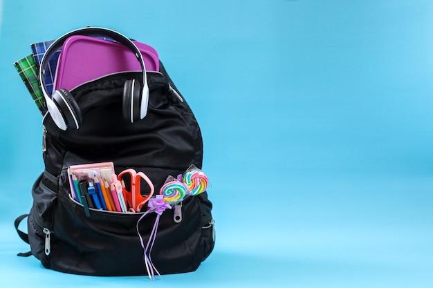 Una mochila escolar con útiles escolares para el concepto de regreso a la escuela con espacio de copia sobre fondo azul.