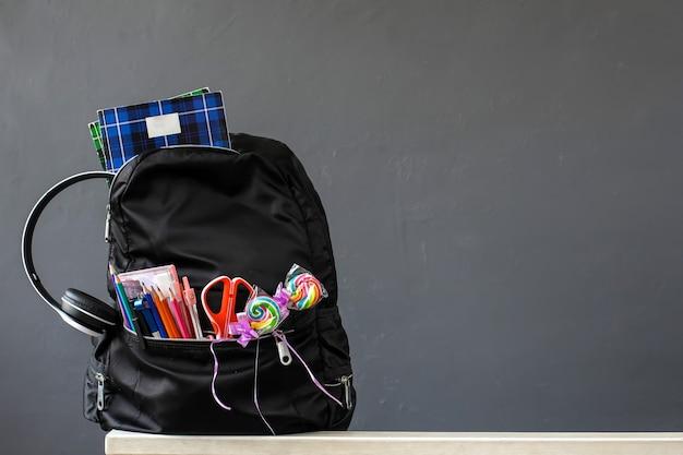 Una mochila escolar con útiles escolares para el concepto de regreso a la escuela con espacio de copia sobre fondo gris