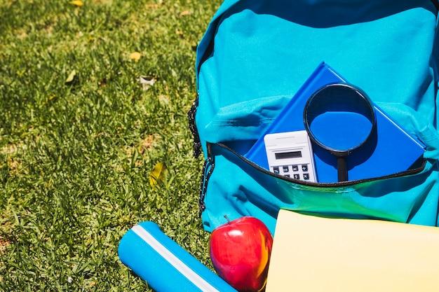 Mochila escolar con útiles escolares sobre hierba.