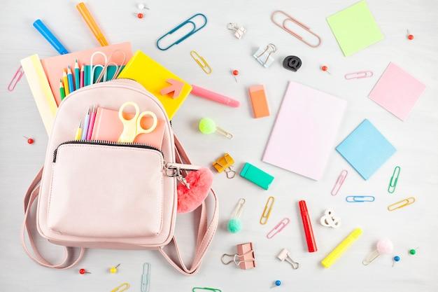 Mochila de estudiante y diversos útiles escolares. estudiar, educar y volver al concepto de la escuela.