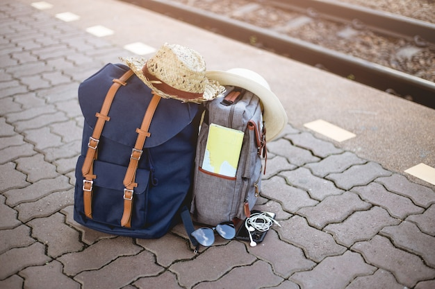 Mochila con gorro, mapa, gafas de sol, auriculares y teléfono inteligente en la estación de tren