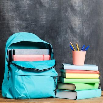 Mochila con libros y bolígrafos.