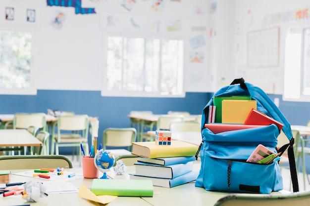 Mochila con libros y papelería dispersa en escritorio.