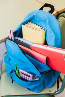 Mochila con libros sobre silla.