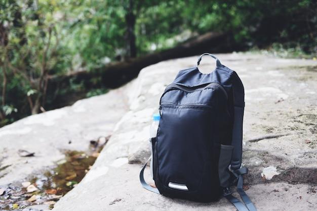Mochila en la naturaleza con botella para excursionista de mochileros en la roca en el bosque en la montaña