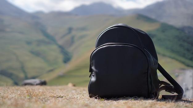 Mochila negra sobre el fondo del monte kazbegi. viajar en georgia - verano