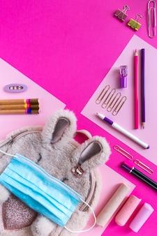 Mochila para niñas con útiles escolares y máscara de protección médica. regreso a la escuela después del concepto de cuarentena, copie el espacio.