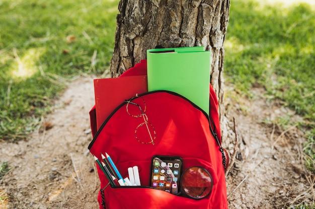 Mochila roja con papelería y teléfono inteligente cerca del árbol.