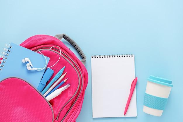 Mochila rosa llena de papelería y taza eco reutilizable sobre fondo azul.