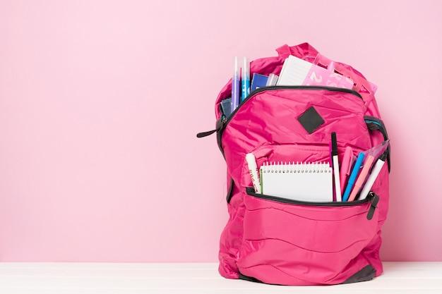Mochila rosa con material escolar.
