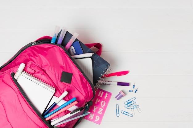 Mochila rosa con útiles escolares vista superior